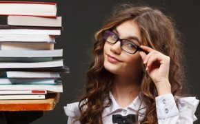 School girl with stack of books over grey background